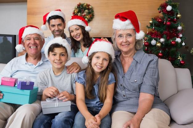 Famille élargie dans des chapeaux de noël avec des boîtes-cadeaux dans le salon Photo Premium