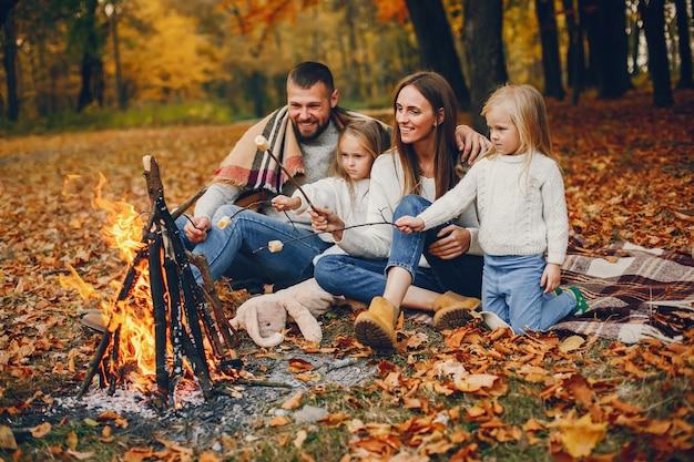Famille avec enfants mignons dans un parc en automne Photo gratuit