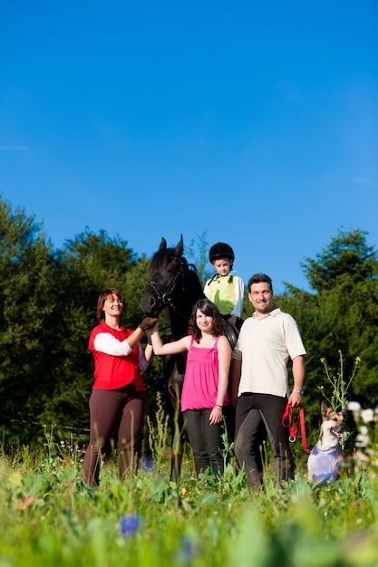 Famille et enfants posant avec un cheval Photo Premium
