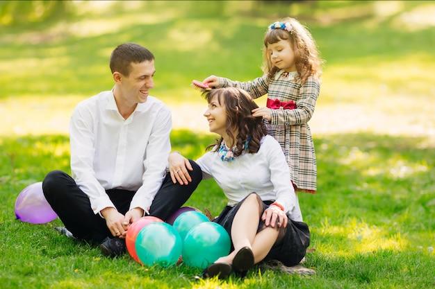 La Famille Est Assise Sur Une Pelouse Avec Des Ballons Photo Premium