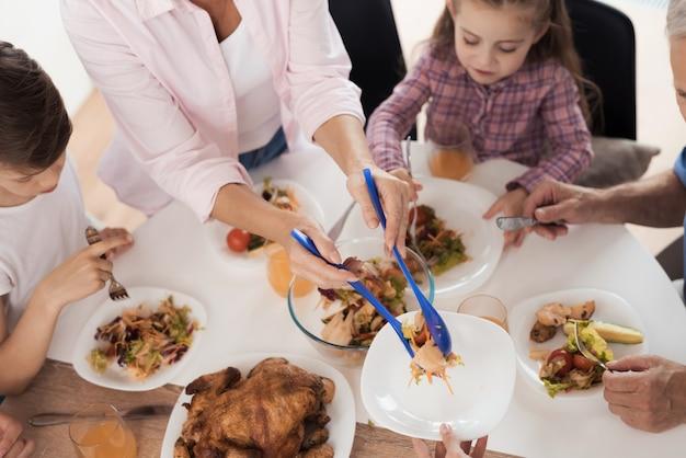 La famille est assise à la table de fête le jour de la bénédiction. Photo Premium