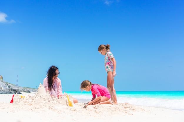 Famille faisant le château de sable à la plage blanche tropicale. mère et deux filles jouant avec du sable sur une plage tropicale Photo Premium