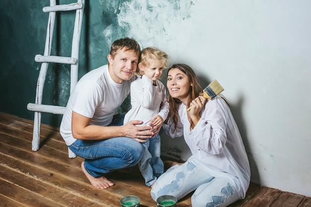 Famille, Fille Heureuse Avec Maman Et Papa Faisant Des Réparations à Domicile, Peindre Les Murs, Avec Amour Photo Premium