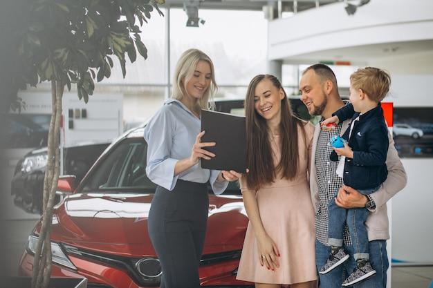Famille avec fils choisir une voiture dans une salle d'exposition Photo gratuit