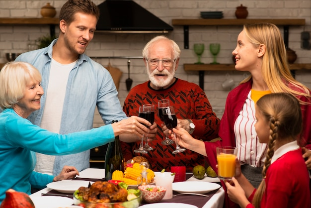 Famille générations portant des verres à griller le jour de thanksgiving Photo gratuit