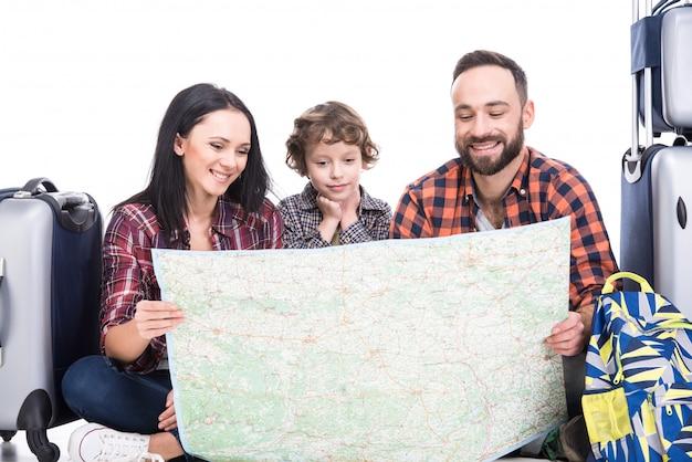Une famille heureuse avec bagages et carte sont prêts à voyager. Photo Premium