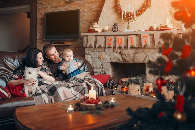 Famille Heureuse Avec Un Bébé Et Un Chien Et à Côté De Lui Une Cheminée à L'affiche De 2017 Photo gratuit
