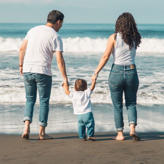 Famille heureuse avec bébé marchant sur la plage et donnant sur la mer Photo gratuit