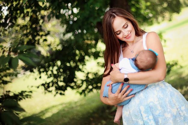Famille heureuse. belle mère joyeuse avec sa fille s'amuser ensemble dans le parc. femme bienveillante allaiter son joli bébé sur la nature. Photo Premium