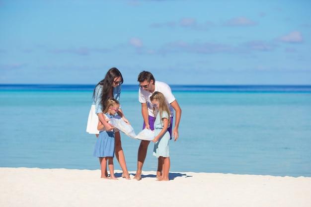 Famille heureuse avec carte sur la plage Photo Premium