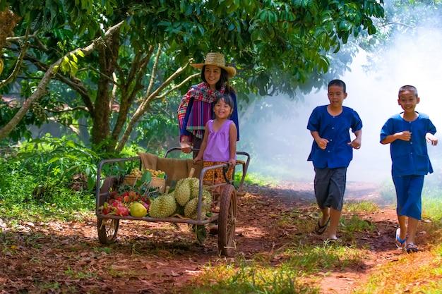 Famille heureuse, cueillette de fruits biologiques frais dans une ferme. Photo Premium