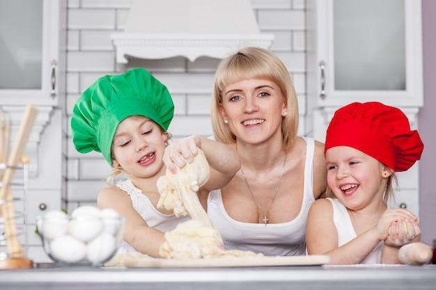Famille heureuse dans la cuisine. mère et enfants préparent la pâte, préparent des biscuits Photo Premium