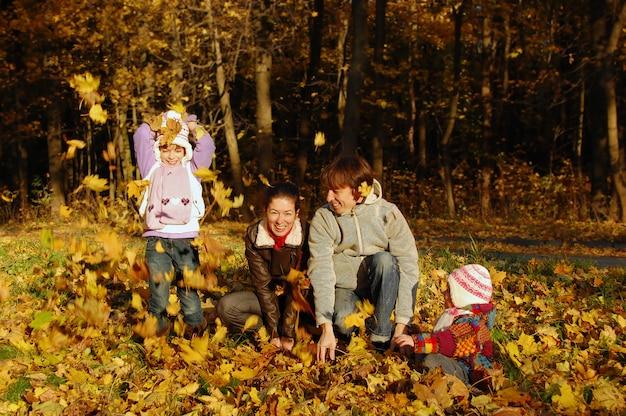 Famille Heureuse Avec Deux Enfants Jetant Des Feuilles Dans Le Parc Automne Photo Premium