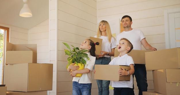 Famille Heureuse, à, Deux Enfants, à, Nouveau, Maison, Tenue, Boîtes Photo Premium
