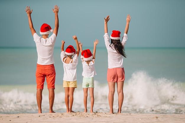 Famille heureuse avec deux enfants à santa hat en vacances d'été Photo Premium
