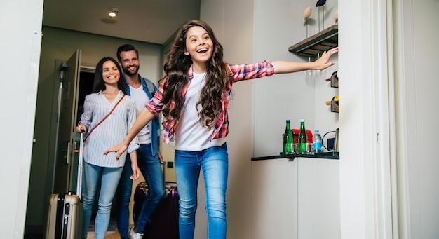 Une Famille Heureuse Entrant Dans La Chambre D'hôtel Photo Premium