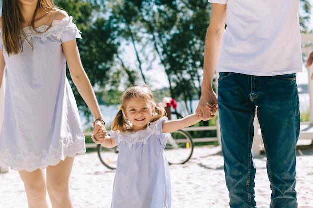 Famille heureuse à l'extérieur de passer du temps ensemble. père, mère et fille s'amusent et courent sur une plage Photo Premium