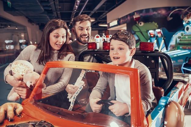 Famille heureuse, fils ravis assis sur une voiture de jouet Photo Premium