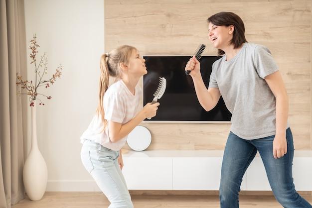 Famille Heureuse Jeune Mère Adulte Et Jolie Fille Adolescente S'amusant Chanter Une Chanson De Karaoké Dans Des Brosses à Cheveux. Photo Premium