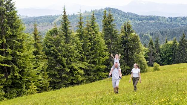 Famille heureuse: père et fils sur les épaules et mère marchant sur un champ verdoyant contre la forêt de conifères et les montagnes. Photo Premium