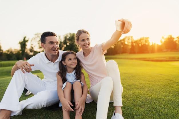 Famille heureuse prend selfie assis sur une pelouse verte. Photo Premium