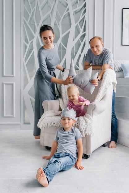 Une Famille Heureuse Reste à La Maison Et Essaie Une Couronne Pour Les Enfants, Le Concept De Jeu Et De Développement Pour Rester à La Maison. Photo Premium