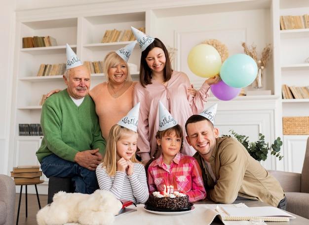 Famille Heureuse De Tir Moyen Posant Avec Un Gâteau Photo gratuit
