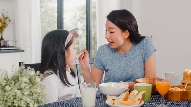 Famille japonaise asiatique prend le petit déjeuner à la maison. asiatique maman et sa fille heureuse de parler ensemble en mangeant du pain, boire du jus d'orange, des céréales de flocons de maïs et du lait sur la table dans la cuisine moderne du matin. Photo gratuit
