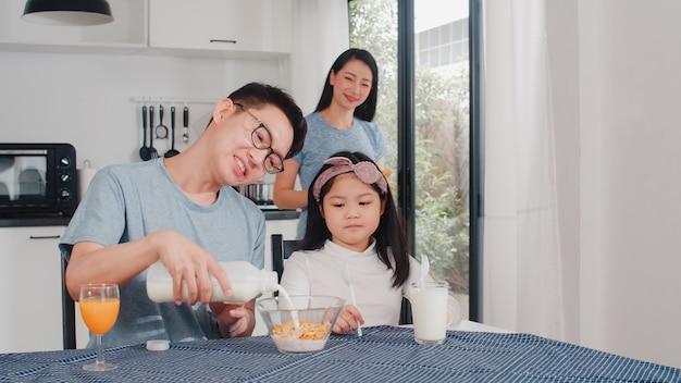 Famille japonaise asiatique prend le petit déjeuner à la maison. maman, papa et fille asiatiques se sentant heureux de parler ensemble tout en mangeant du pain, des céréales de flocons de maïs et du lait dans un bol sur la table dans la cuisine le matin. Photo gratuit