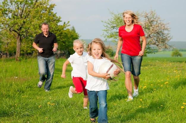Famille jouant au ballon Photo Premium