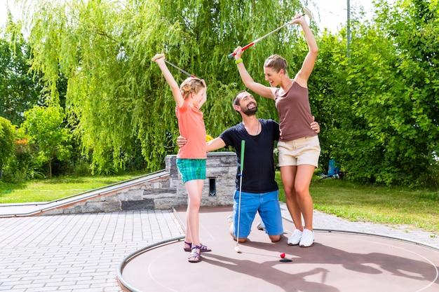 Famille jouant au golf miniature en plein air Photo Premium