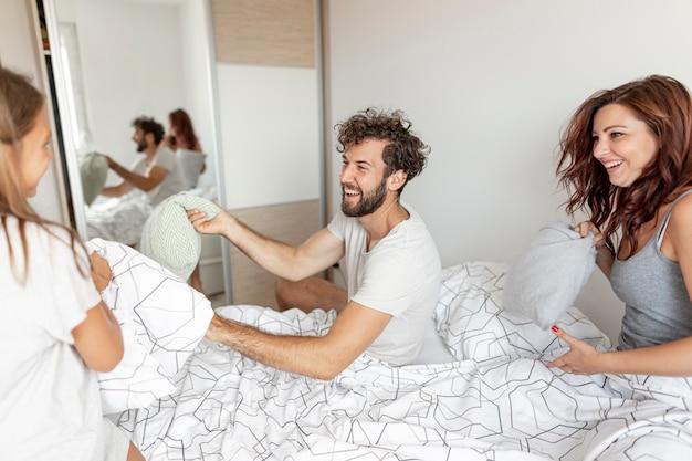 Famille jouant avec des oreillers au lit Photo gratuit