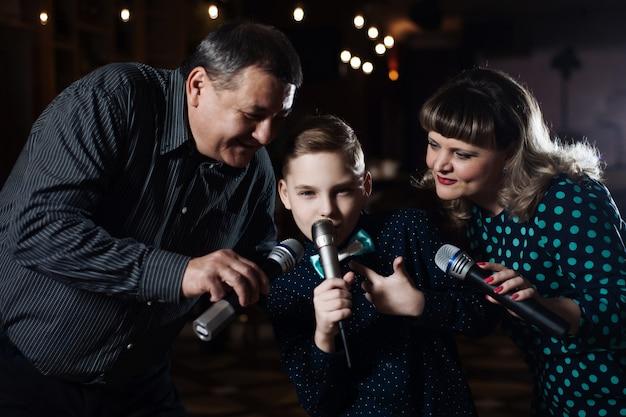 Famille karaoké. portrait d'une famille heureuse, chantant au micro Photo Premium