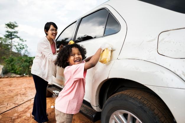 Famille lavant leur voiture blanche Photo Premium