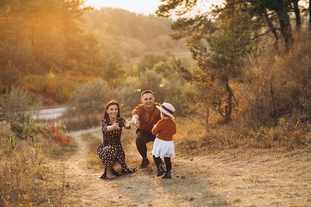 Famille avec leur petite fille dans un champ d'automne Photo gratuit