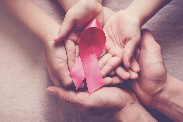 Famille mains tenant un ruban rose, sensibilisation au cancer du sein Photo Premium