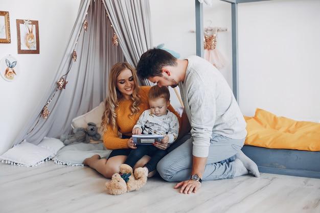 Famille à la maison assis sur le sol Photo gratuit