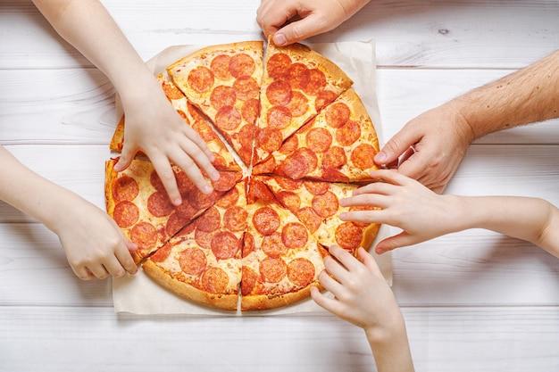 Famille mangeant de la pizza au peperoni. enfants et pères tenant une part de pizza. Photo Premium