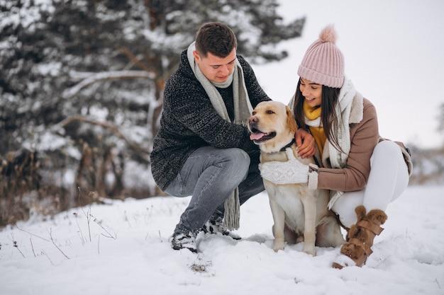 Famille marchant dans un parc d'hiver avec leur chien Photo gratuit