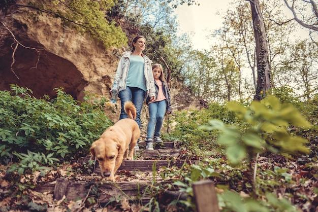 Famille marchant en forêt avec un chien Photo Premium
