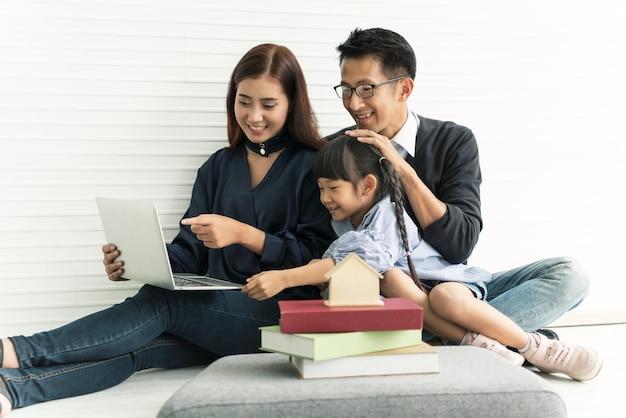 Famille mère asiatique et père avec fille heureux ensemble dans la salle de séjour à la maison. Photo Premium