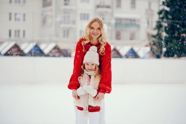 Famille mignonne et belle dans une ville d'hiver Photo gratuit