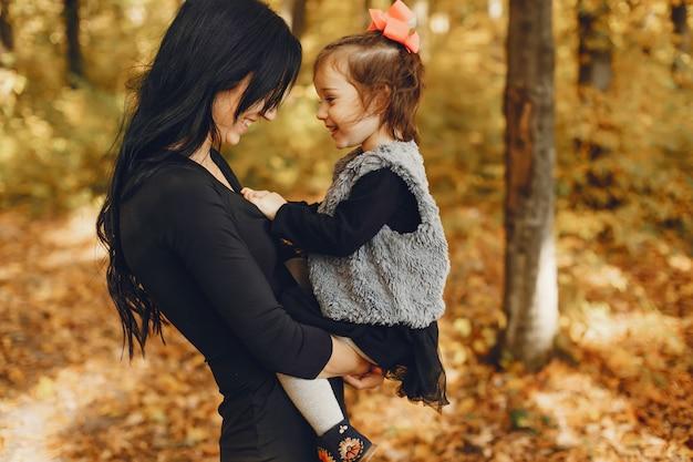 Famille mignonne et élégante dans un parc en automne Photo gratuit