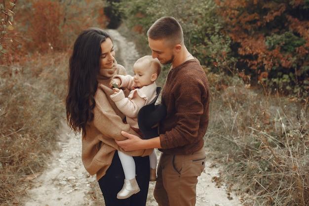 Famille mignonne et élégante jouant dans un champ d'automne Photo gratuit