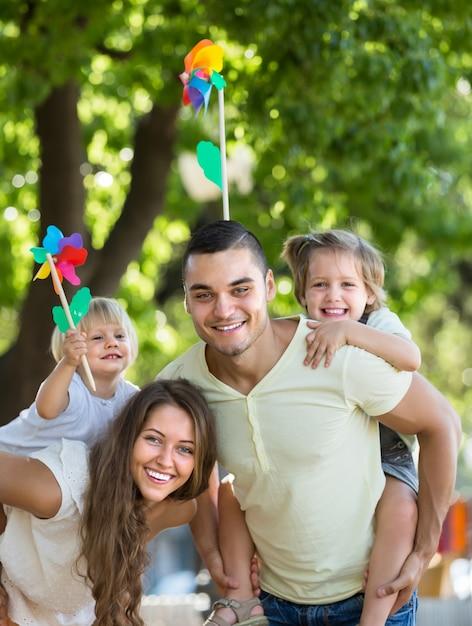 Famille avec des moulins à vent de jouet au parc Photo gratuit