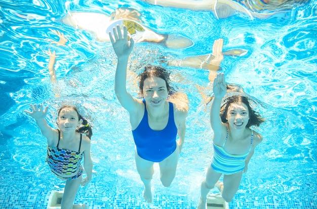 Famille nage dans la piscine sous l'eau, heureuse mère active et les enfants s'amusent sous l'eau, fitness et sport avec les enfants en vacances d'été sur la station Photo Premium