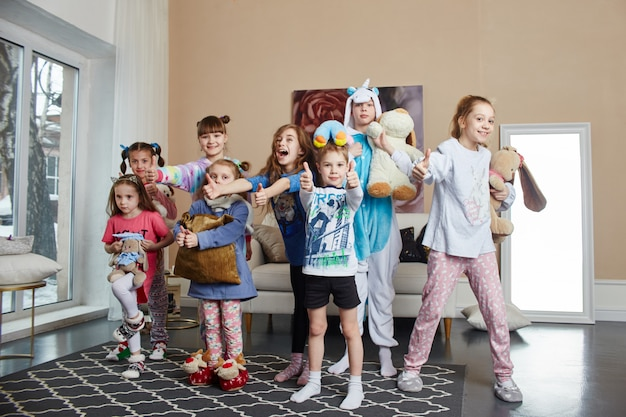 Famille nombreuse, les enfants s'amusent et jouent le matin à la maison. garçons et filles en pyjama de nuit Photo Premium