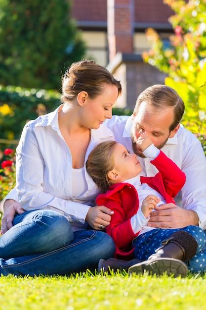Famille sur la pelouse du jardin Photo Premium