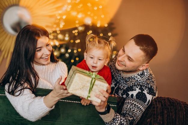Famille Avec Petite Fille Assise Devant Un Arbre De Noël Et Une Boîte-cadeau Déballée Photo gratuit