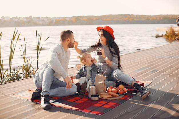 Famille avec petite fille assise près de l'eau dans un parc en automne Photo gratuit